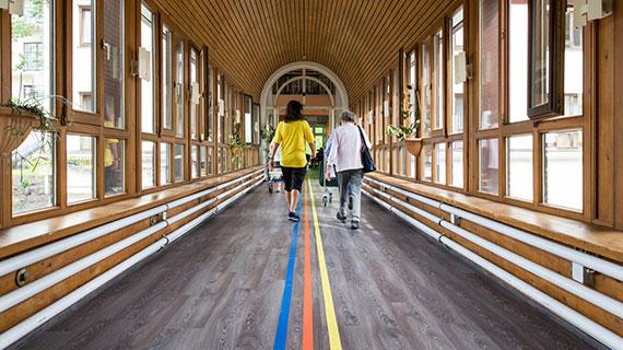 Zwei Menschen gehen durch einen langen Flur mit einem Farbleitsystem.