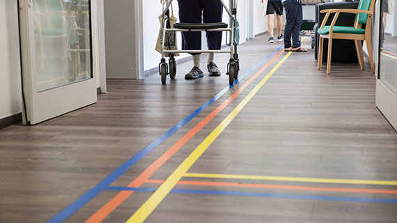 Ein älterer Mensch geht an einem Rollator durch einen Flur mit einem Farbleitsystem.