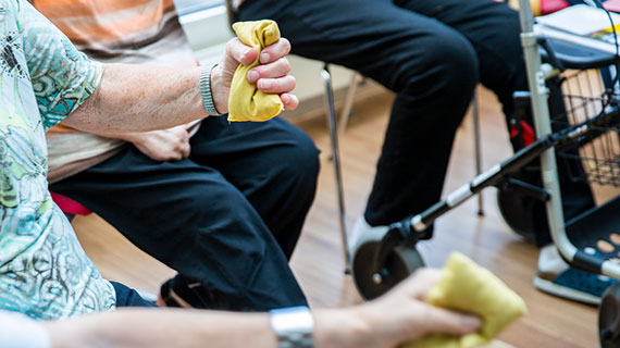 Bei der Sitzgymnastik. Die Teilnehmer drücken Schwämme in der Hand.