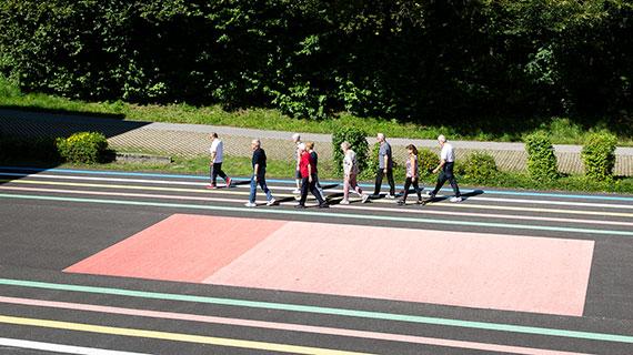 Gruppenfoto: Heinz Gaier geht mit einer Gruppe Menschen auf einem Sportplatz.