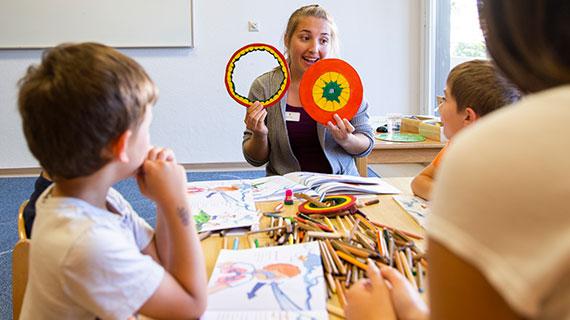 Eine Therapeutin zeigt Kindern runde Scheiben.