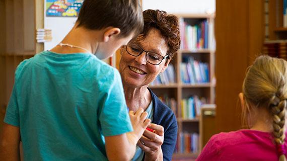 In der Grundschule: Eine Frau unterhält sich lächelnd mit einem Jungen.