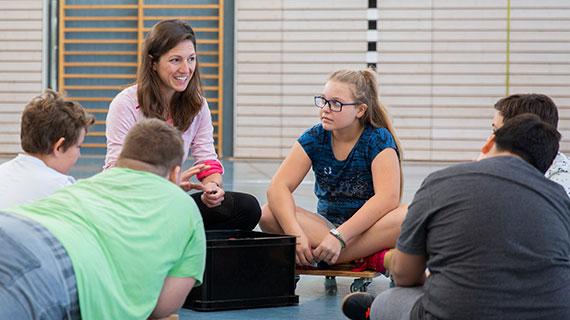 Gruppenfoto: Eine Frau sitzt mit mehreren Jugendlichen in einer Turnhalle.