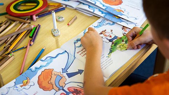 Ein Kind malt Figuren in einem Malheft aus.
