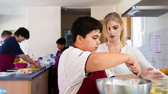 In der Küche: Ein Junge rührt in einer Schüssel; eine junge Frau schaut ihm zu.