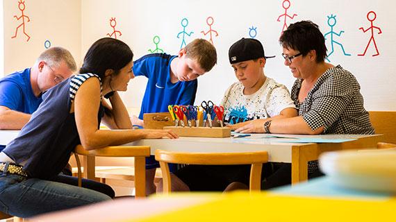 Mehrere Jugendliche und Erwachsene gemeinsam am Basteltisch.