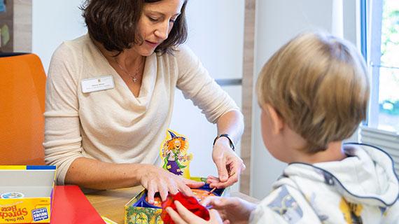 Eine Frau spielt mit einem Jungen an einem kleinen Tisch.