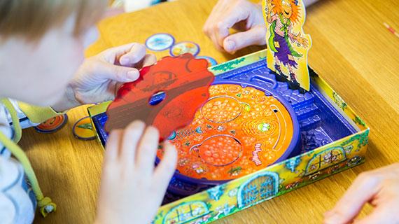 Ein Junge beugt sich über ein Spiel und hält eine bunte Scheibe in der Hand.