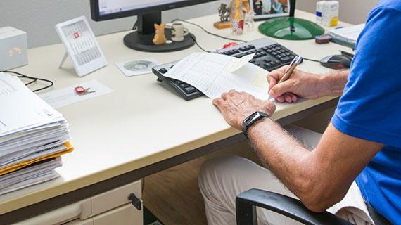 Ein Arzt sitzt am Schreibtisch und füllt ein Dokument aus.