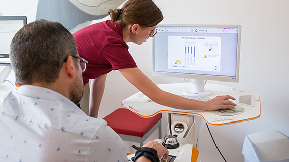Patient und Therapeutin sehen gemeinsam Daten auf einem Bildschirm an.