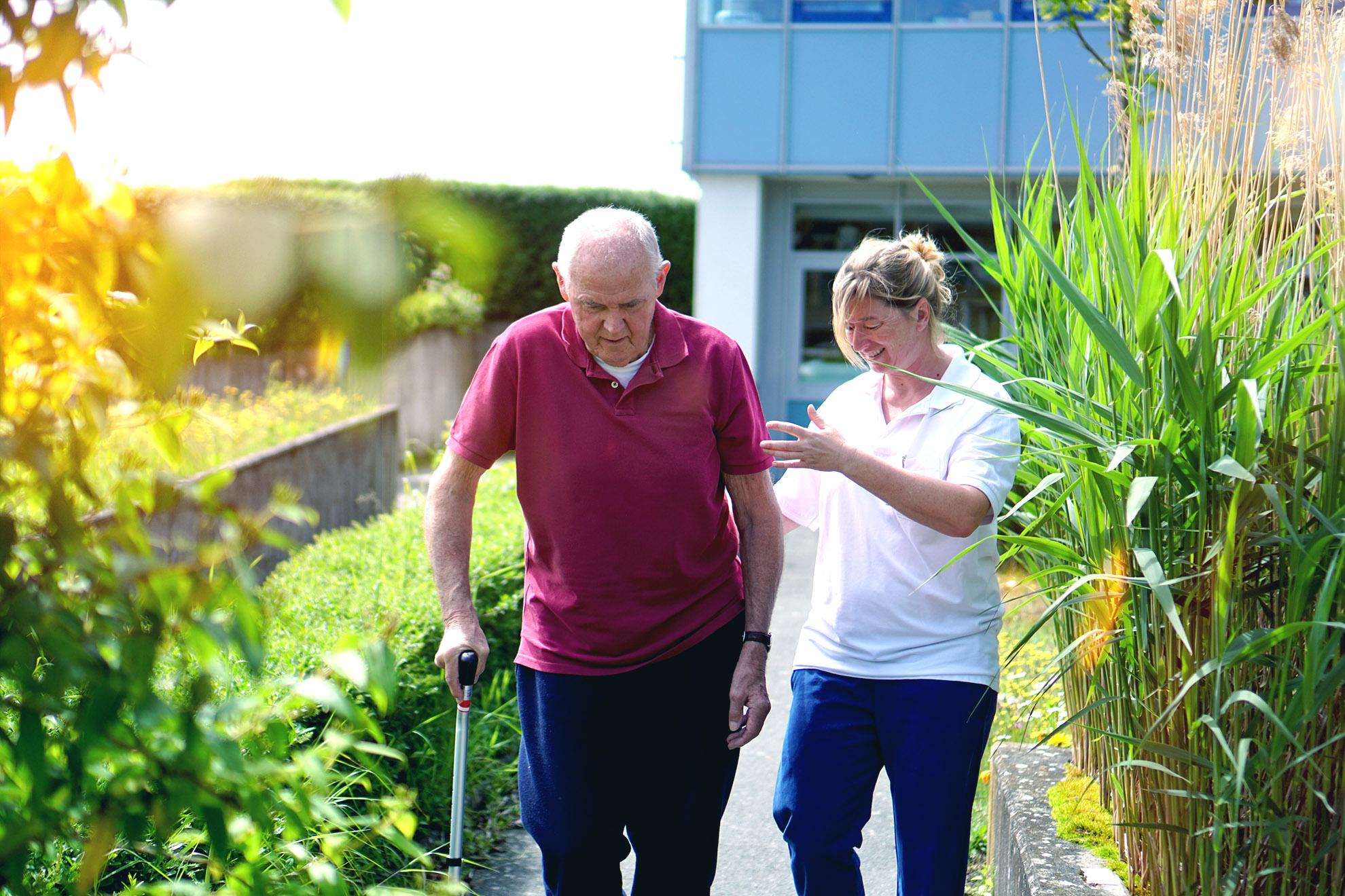Reinhard Bischoff lernt mithilfe einer Therapeutin wieder laufen.