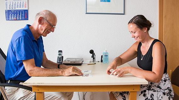 Logopäde Holger Grötzbach und eine Patientin sitzen an einem Tisch.