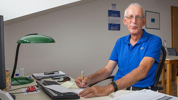 Holger Grötzbach arbeitet an seinem Schreibtisch.