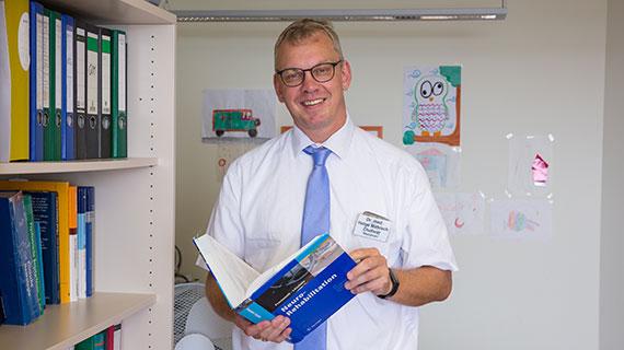 Porträtfoto: Helge Matrisch lächelt in die Kamera.