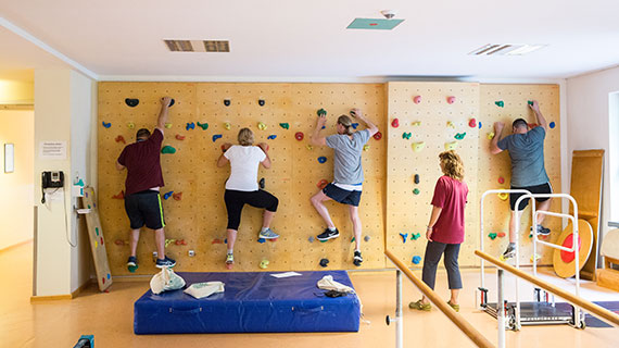 Im Therapieraum: Mehrere Menschen üben an einer Kletterwand.
