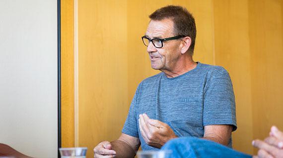 Porträt: Hans-Reiner P. sitzt mit anderen Personen an einem Tisch