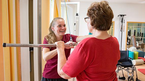 Anja Riebesecker trainiert mit einer Patientin in einem Sportraum