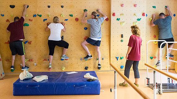 Patienten machen Übungen an einer Kletterwand