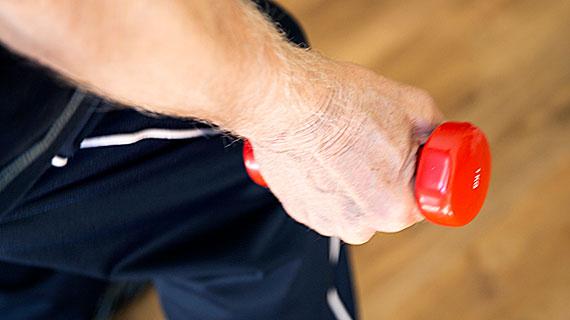 Eine Hand greift eine rote Hantel.
