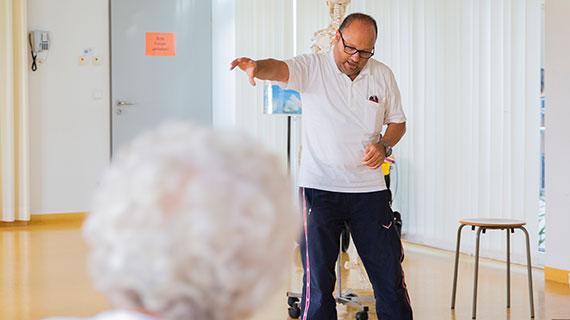 Alternativtext: Physiotherapeut führt Übungen vor.