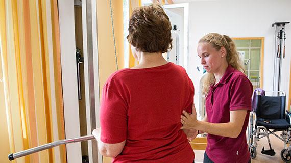 AlternativtextIn der Reha-Klinik: Eine Therapeutin korrigiert die Haltung einer Patientin.