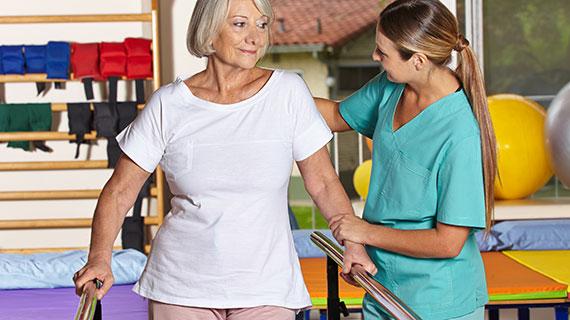 Therapie-Situation: Eine Therapeutin hilft ihrer Patientin beim Gehen an einem Übungsgerät.