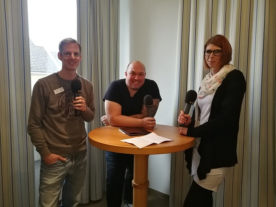 Logopäde Simon Oppenberg (links) und Pflegekraft Jessica Pilz (rechts) sprechen mit Moderator Gordon Schönwälder (mitte) über die Arbeit mit beatmeten Patienten/innen.